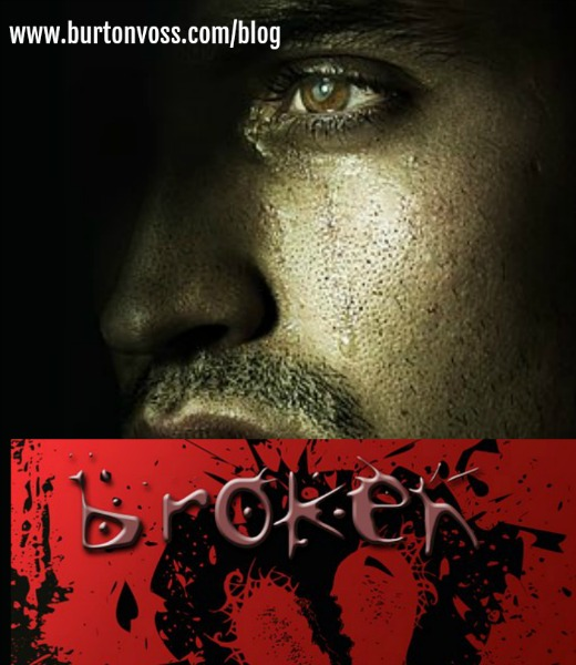 "Dark view of man's face with tear track. Lower half of picture is in red with the word ""broken"" above a drawing of a heart."